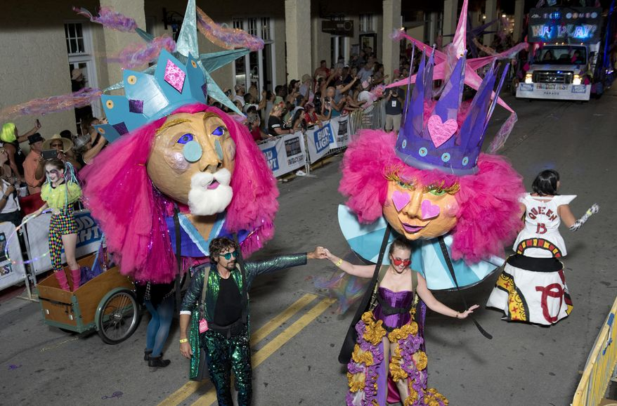 In this Saturday, Oct. 27, 2018, photo provided by the Florida Keys News Bureau, revelers supporting king and queen puppets make their way up Duval Street during the Fantasy Fest Parade in Key West, Fla. The extravaganza was the highlight event of the 10-day Fantasy Fest costuming and masking festival that ends Sunday, Oct. 28. (Rob O'Neal/Florida Key News Bureau via AP)