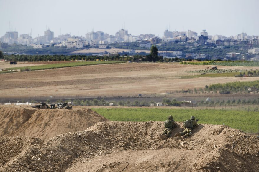 Israeli soldiers observe the Gaza Strip border, Saturday, Oct. 27, 2018. The Israeli military has struck dozens of targets across the Gaza Strip in response to heavy rocket fire and threatened to expand its air campaign to Syria after accusing Iranian forces in Damascus of orchestrating the rocket attacks. (AP Photo/Tsafrir Abayov)
