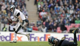 Philadelphia Eagles quarterback Carson Wentz (11) skips out of a tackle during the second half of an NFL football game against Jacksonville Jaguars at Wembley stadium in London, Sunday, Oct. 28, 2018. (AP Photo/Matt Dunham)