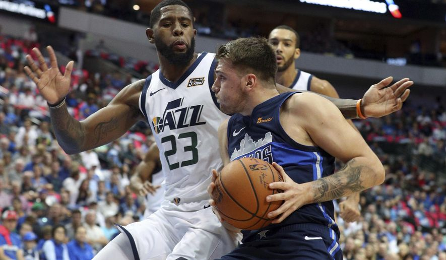 Utah Jazz forward Royce O'Neale (23) defends as Dallas Mavericks forward Luka Doncic (77) tries to drive toward the basket in the first half of an NBA basketball game Sunday, Oct. 28, 2018, in Dallas. (AP Photo/Richard W. Rodriguez)