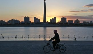 """In this Saturday, Oct. 27, 2018 photo, a man rides his electric bike as the Tower of the Juche Idea is silhouetted agains the sunrise in Pyongyang, North Korea. North Korea is exploring a grand plan to become a regional transportation hub, inspired in part by the successes of Singapore and Switzerland, and would be open to joining world financial institutions such as the International Monetary Fund if current member states give up their """"hostile"""" policies toward it, a senior government economist has told The Associated Press. (AP Photo/Dita Alangkara)"""