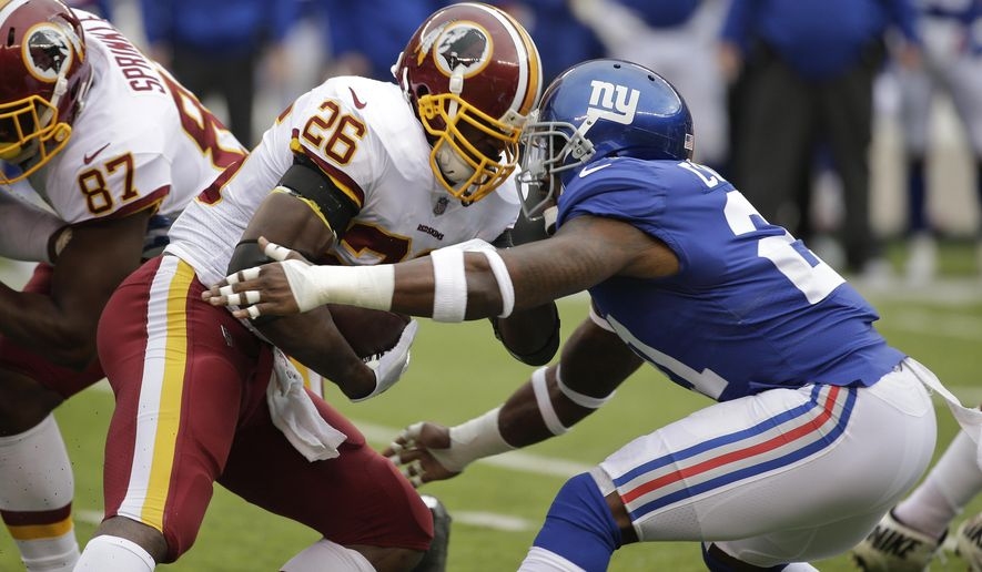 Washington Redskins running back Adrian Peterson (26) is hit by New York Giants strong safety Landon Collins (21) during the first quarter of an NFL football game, Sunday, Oct. 28, 2018, in East Rutherford, N.J. (AP Photo/Seth Wenig)