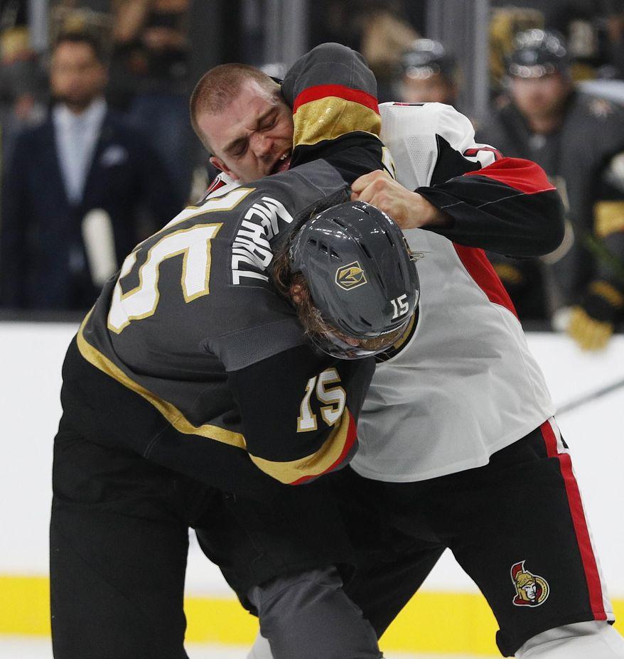 Vegas Golden Knights defenseman Jon Merrill (15) fights with Ottawa Senators defenseman Mark Borowiecki (74) during the first period of an NHL hockey game Sunday, Oct. 28, 2018, in Las Vegas. (AP Photo/John Locher)