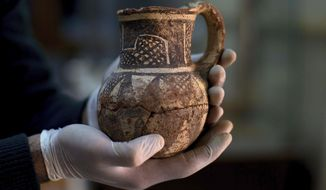 "In this Feb. 23, 2016 file photo, Jihad Abu Kahrlah, an archeologist at Syria's National Museum, holds an artifact delivered from the Daraa Museum to Damascus, Syria. Syrian officials have reopened the country's National Museum in Damascus, more than six years after the prominent institution was shut down. Syria's Culture Minister Mohamed al-Ahmad told reporters Sunday, Oct. 28, 2018 that the reopening sends a ""genuine message"" that Syria's heritage has not been affected by ""terrorism."" (AP Photo/Hassan Ammar, File)"