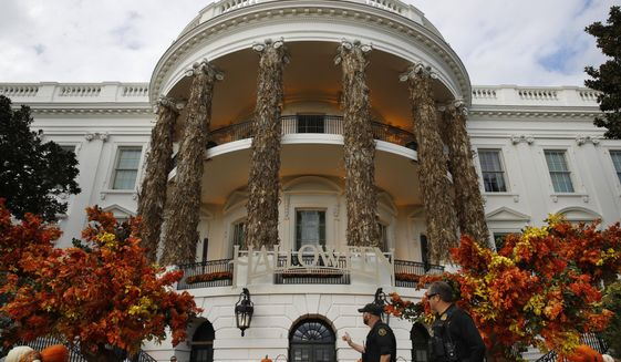 Secret Service police walk past the South Portico of the White House decorated for Halloween, Sunday, Oct. 28, 2018, in Washington. President Donald Trump and first lady Melania Trump will greet children this afternoon during a Halloween event at the White House. (AP Photo/Jacquelyn Martin)