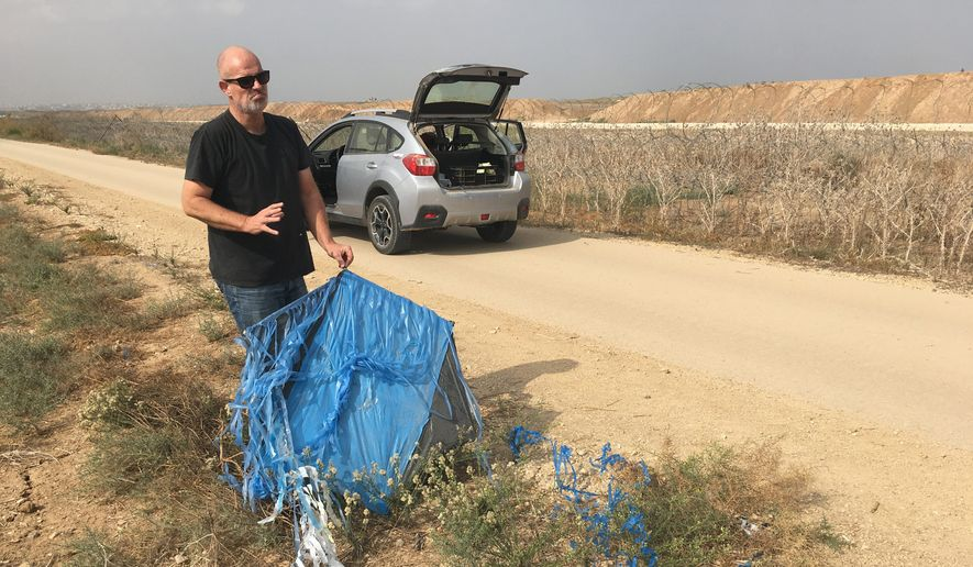 David Bing, a farmer from Kibbutz Kfar Aza, finds an incendiary kite on his farm fields, sent over from Gaza with the intention of starting fires in Israel. (photograph by Laura Kelly)