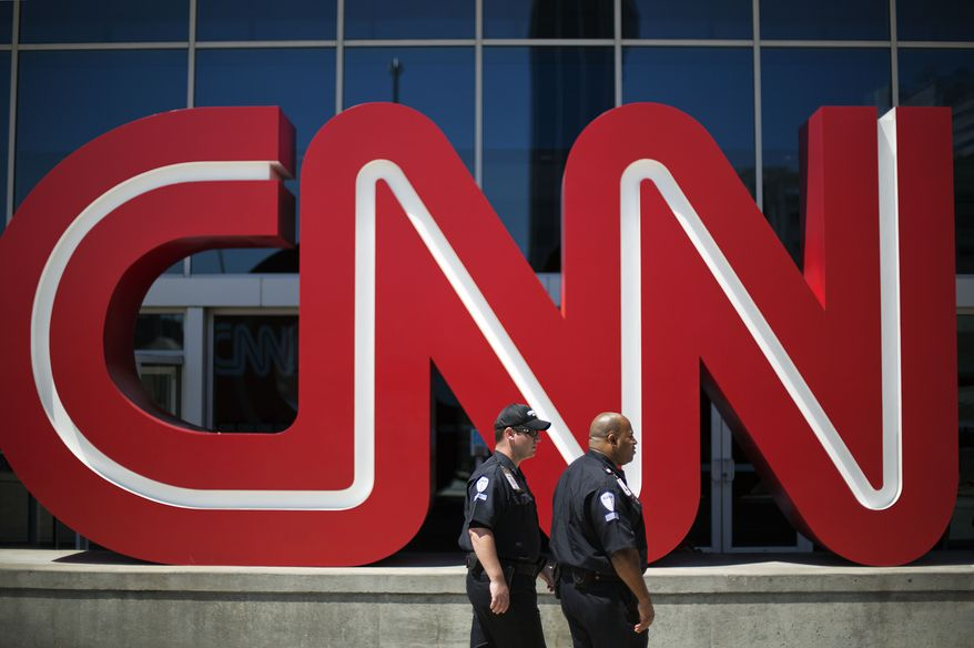 In this Aug. 26, 2014 file photo, security guards walk past the entrance to CNN headquarters in Atlanta.  (AP Photo/David Goldman, File) **FILE**