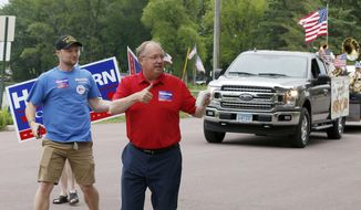 In this June 10, 2018, file photo, Minnesota 1st District Congressional candidate Jim Hagedorn gives a thumbs up as he works a parade in Waterville, Minn. (AP Photo/Jim Mone, File)