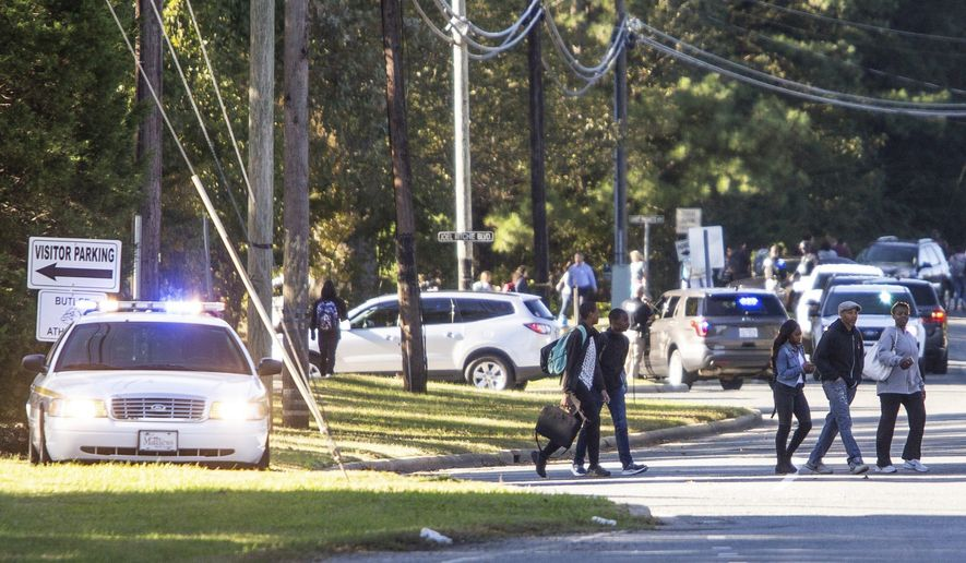 Parents walked to go pick up their kids outside Butler High School after the scene was considered safe in Matthews, N.C., Monday, Oct. 29, 2018. A student shot and killed a fellow student during a fight in a crowded school hallway Monday, officials said, prompting a lockdown and generating an atmosphere of chaos and fear as dozens of parents rushed to the school to make sure their children were safe.  (Joshua Komer/The Charlotte Observer via AP)