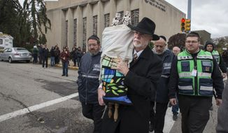Rabbi Jeffrey Myers, center, of Tree of Life Synagogue carries their Torah to be stored elsewhere in Pittsburgh on Monday, October 29, 2018. The man accused in the Pittsburgh synagogue massacre appeared briefly in federal court in a wheelchair and handcuffs Monday to face charges he killed 11 people in what is believed to be the deadliest attack on Jews in U.S. history. (Charles Fox/The Philadelphia Inquirer via AP)