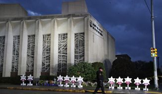 In this Oct. 28, 2018, file photo a Pittsburgh Police officer walks past the Tree of Life Synagogue and a memorial of flowers and stars in Pittsburgh in remembrance of those killed and injured when a shooter opened fire during services Saturday at the synagogue. (AP Photo/Gene J. Puskar, File)