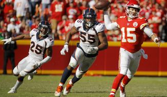 Kansas City Chiefs quarterback Patrick Mahomes (15) is pursued by Denver Broncos linebacker Bradley Chubb (55) and cornerback Bradley Roby (29) during the second half of an NFL football game in Kansas City, Mo., Sunday, Oct. 28, 2018. (AP Photo/Charlie Riedel)
