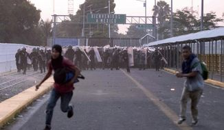 Central American migrants run from Mexican authorities during clashes on a border bridge that connects Guatemala and Mexico, in Tecun Uman, Guatemala, Sunday, Oct. 28, 2018. A new group of migrants, who called themselves a second caravan, gathered on a bridge after forcing their way through a gate at the Guatemalan end. (AP Photo/Santiago Billy)