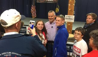 In this Friday, Oct. 26,2018 photo Republican Senate candidate Matt Rosendale poses for a photograph with supporters after a rally in East Helena, Mont. Rosendale is in a tight race against incumbent Democratic Sen. Jon Tester. (AP Photo/Matt Volz)