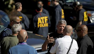 Law enforcement officials gather outside a U.S. post office facility after reports that a suspicious package was found in Atlanta, Monday, Oct. 29, 2018. The FBI said authorities recovered the suspicious package that was address to the cable network CNN. (AP Photo/David Goldman)