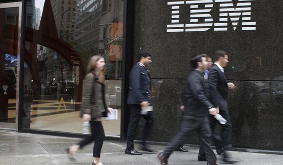 In this April 26, 2017, file photo, pedestrians walk past the IBM logo displayed on the IBM building in New York. Shares of Red Hat skyrocketed at the opening bell Monday, Oct. 29, 2018, after IBM, in the biggest acquisition in its 100-year history, acquired the software company. (AP Photo/Mary Altaffer, File) **FILE**