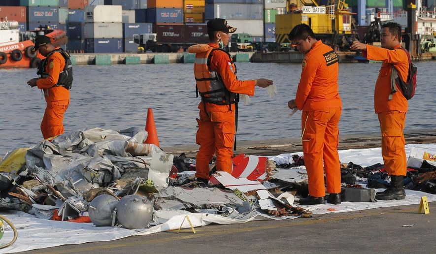 FILE- In this Monday, Oct. 29, 2018, file photo members of Indonesian Search and Rescue Agency (BASARNAS) inspect debris recovered from near the waters where a Lion Air passenger jet is suspected to crash, at Tanjung Priok Port in Jakarta, Indonesia. A Lion Air flight crashed into the sea just minutes after taking off from Indonesia's capital on Monday. The deadly crash has renewed questions about the safety of Indonesian airlines soon after U.S. and European regulators removed prohibitions against them. (AP Photo/Tatan Syuflana, File)