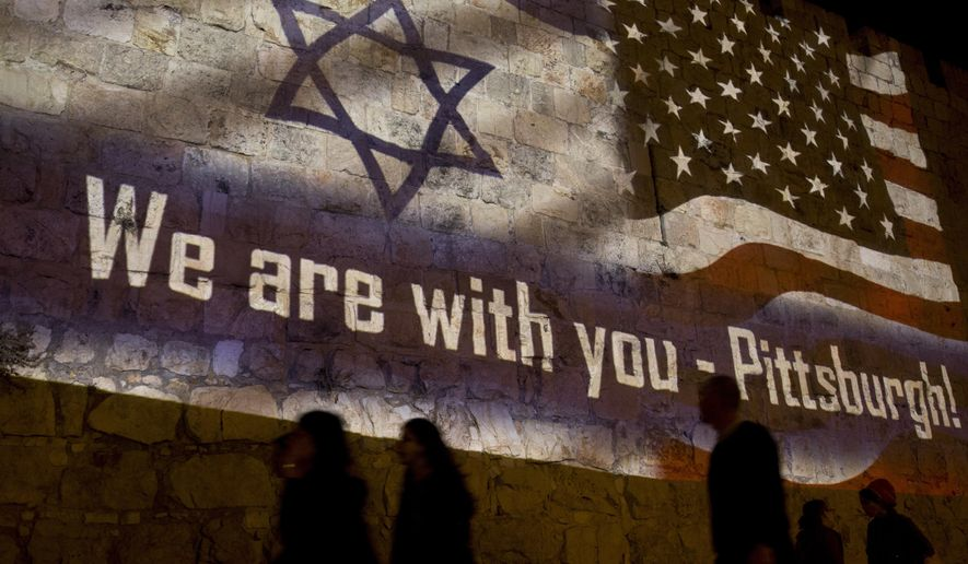 People walk past a projection on the Old City wall in Jerusalem, Sunday, Oct. 28, 2018 in a commemoration of the victims of a deadly shooting at a Pittsburgh synagogue. A shooter opened fire at a Pittsburgh synagogue, killing 11 people in one of the deadliest attacks on Jews in U.S. history. (AP Photo/Dusan Vranic)