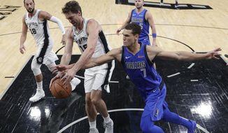 San Antonio Spurs center Pau Gasol (16) and Dallas Mavericks forward Dwight Powell (7) scramble for a rebound during the first half of an NBA basketball game, Monday, Oct. 29, 2018, in San Antonio. (AP Photo/Eric Gay)