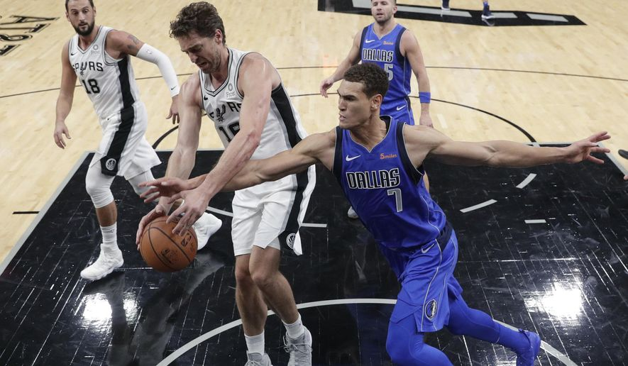 San Antonio Spurs center Pau Gasol (16) and Dallas Mavericks forward Dwight Powell (7) scramble for a rebound during the first half of an NBA basketball game, Monday, Oct. 29, 2018, in San Antonio. (AP Photo/Eric Gay)