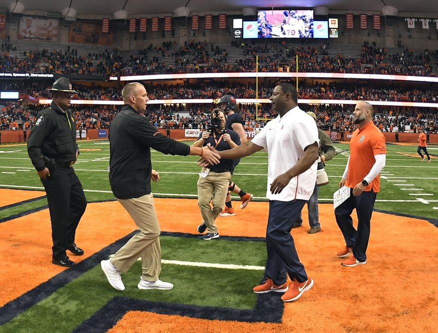 NC State head coach Dave Doeren, left, shakes hands with Syracuse head coach Dino Babers after an NCAA college football game in Syracuse, N.Y., Saturday, Oct. 27, 2018. Syracuse defeated NC State 51-41. (AP Photo/Adrian Kraus)