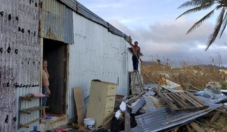 This photo released by Edwin Propst shows a man repairing damage to a home from Super Typhoon Yutu in Saipan, an island of the Northern Mariana Islands, Monday, Oct. 29, 2018. Elections are being postponed by a week in a Pacific U.S. territory still without electricity after a super typhoon destroyed homes, toppled trees, utility poles and left a woman dead. (Edwin Propst via AP)