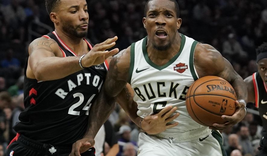 Milwaukee Bucks' Eric Bledsoe tries to drive past Toronto Raptors' Norman Powell during the second half of an NBA basketball game Monday, Oct. 29, 2018, in Milwaukee. (AP Photo/Morry Gash)
