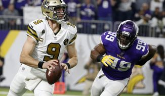 New Orleans Saints quarterback Drew Brees runs from Minnesota Vikings defensive end Danielle Hunter, right, during the second half of an NFL football game, Sunday, Oct. 28, 2018, in Minneapolis. (AP Photo/Bruce Kluckhohn)