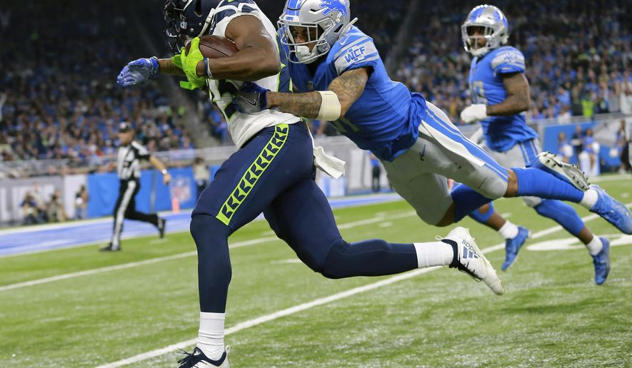 Detroit Lions cornerback Teez Tabor, right, pulls down Seattle Seahawks wide receiver David Moore during the second half of an NFL football game, Sunday, Oct. 28, 2018, in Detroit. (AP Photo/Rey Del Rio)