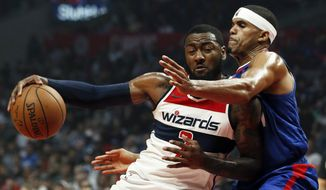 Washington Wizards guard John Wall, left, drives into Los Angeles Clippers forward Tobias Harris during the first half of an NBA basketball game in Los Angeles, Sunday, Oct. 28, 2018. (AP Photo/Alex Gallardo)