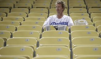 A Los Angeles Dodgers fan sits in the stands after Game 5 of baseball's World Series against the Los Angeles Dodgers on Sunday, Oct. 28, 2018, in Los Angeles. The Red Sox won 5-1 to win the series 4 game to 1. (AP Photo/Jae C. Hong)