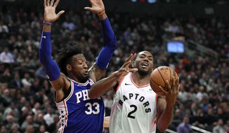 Toronto Raptors forward Kawhi Leonard (2) is fouled by Philadelphia 76ers forward Robert Covington (33) during the first half of an NBA basketball game, Tuesday, Oct. 30, 2018 in Toronto. (Nathan Denette/The Canadian Press via AP)