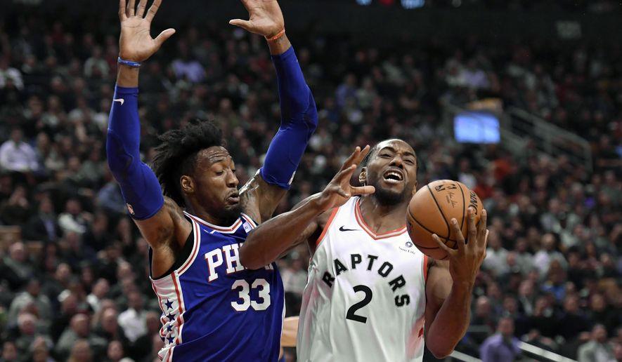 Toronto Raptors forward Kawhi Leonard (2) is fouled by Philadelphia 76ers forward Robert Covington (33) during the first half of an NBA basketball game, Tuesday, Oct. 30, 2018 in Toronto. (Nathan Denette/The Canadian Press via AP)