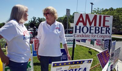 In this Thursday, June 14, 2018, file photo, Amie Hoeber, right, a Republican who is running in the Maryland 6th Congressional District primary, talks to a supporter at an early voting center in Frederick, Md. (AP Photo/Brian Witte)