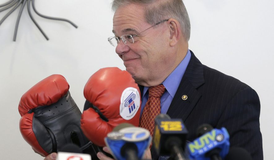 """Democratic Sen. Bob Menendez receives a gift of boxing gloves before speaking to a group of mostly seniors in Bloomfield, N.J., Tuesday, Oct. 30, 2018. Menendez has cast Republican rival Bob Hugin as President Donald Trump's closest Senate ally-in the-making, but the former drug company executive said he's """"no Trump Republican"""" and bashed him over tossed-out corruption charges in the closely watched contest. (AP Photo/Seth Wenig)"""