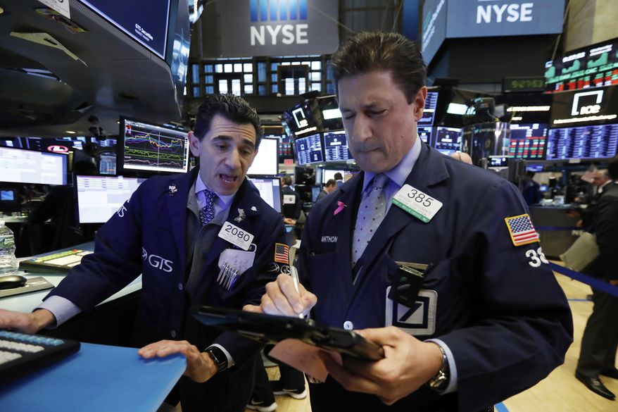 In this Oct. 24, 2018, file photo, specialist Peter Mazza, left, and trader Anthony Carannante work on the floor of the New York Stock Exchange. (AP Photo/Richard Drew, File)