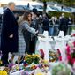 First lady Melania Trump, accompanied by President Donald Trump, and Tree of Life Rabbi Jeffrey Myers, right, puts down a white flower at a memorial for those killed at the Tree of Life Synagogue in Pittsburgh, Tuesday, Oct. 30, 2018. (AP Photo/Andrew Harnik)