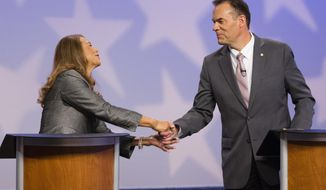 Cristina McNeil and former state Sen. Russ Fulcher, R-Meridian, shake hands after a debate at the studios of Idaho Public Television in Boise, Idaho, Sunday, Oct. 28, 2018. (AP Photo/Otto Kitsinger)