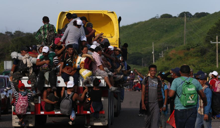 Migrants hitch rides on passing trucks, in Niltepec, Oaxaca state, Mexico, Tuesday, Oct. 30, 2018. The migrant caravan slowly advancing through southern Mexico is demanding that the Mexican government help its 4,000-some members reach Mexico City. (AP Photo/Rebecca Blackwell)