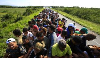 Hundreds of migrants hitch a ride in a truck between Niltepec and Juchitan, Mexico, Tuesday, Oct. 30, 2018. The migrant caravan slowly advancing through southern Mexico is demanding that the Mexican government help its 4,000-some members reach Mexico City. (AP Photo/Rebecca Blackwell)