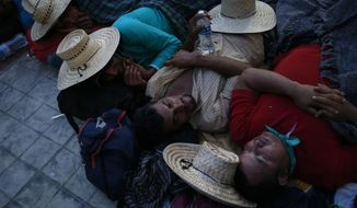 """Migrants sleep packed together in a church courtyard at nightfall, as a thousands-strong caravan of Central Americans hoping to reach the U.S. border stops for the night in Niltepec, Oaxaca state, Mexico, Monday, Oct. 29, 2018. As the caravan resumed its slow advance Monday, still at least 1000 miles or farther from the U.S., the Pentagon announced it would send 5,200 active-duty troops to """"harden"""" the border.(AP Photo/Rebecca Blackwell)"""