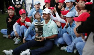 Xander Schauffele of the United States poses with the trophy near the golf course staff after winning the HSBC Champions golf tournament held at the Sheshan International Golf Club in Shanghai, Sunday, Oct. 28, 2018. (AP Photo/Ng Han Guan)