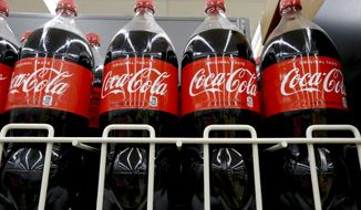 FILE- In this Aug. 8, 2018, file photo bottles of Coca-Cola sit on a shelf in a market in Pittsburgh. The Coca-Cola Co. reports earnings Tuesday, Oct. 30. (AP Photo/Gene J. Puskar, File)