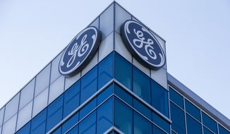 In this Jan. 16, 2018, file photo, the General Electric logo is displayed at the top of their Global Operations Center, in the Banks development of downtown Cincinnati. General Electric Co. reports earnings Tuesday, Oct. 30. (AP Photo/John Minchillo, File)