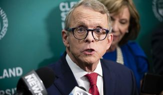 FILE - In this Oct. 8, 2018, file photo, Ohio Attorney General and Republican gubernatorial candidate Mike DeWine answers questions from the media in the spin room following a debate with Democratic gubernatorial candidate Richard Cordray at Cleveland State University, in Cleveland. Locked in a tight race for governor in the perennial swing state of Ohio, DeWine and Cordray are using the final stretch to hedge their bets on Donald Trump. (AP Photo/Angelo Merendino, File)