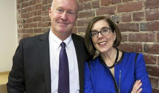 In this Tuesday, Oct. 30, 2018 photo, the Oregon Independent Party's gubernatorial candidate, Patrick Starnes, left, poses for a photo with Oregon Democratic incumbent Gov. Kate Brown at Brown's Portland, Ore., campaign office. Starnes announced Tuesday he was withdrawing from the race and endorsing Brown, who is in a tight race with GOP challenge state Rep. Knute Buehler. (AP Photo/Gillian Flaccus)