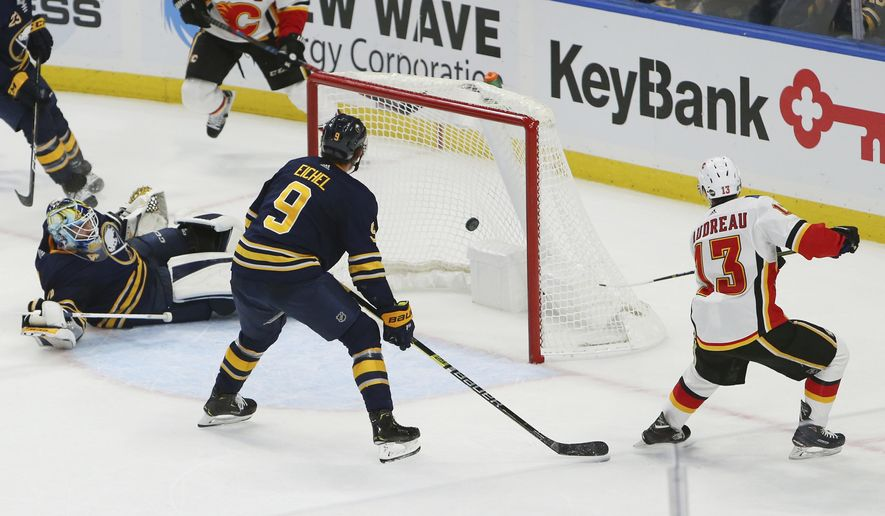 Calgary Flames forward Johnny Gaudreau (13) puts the puck past Buffalo Sabres goalie Carter Hutton (13) during the overtime period of an NHL hockey game, Tuesday, Oct. 30, 2018, in Buffalo, N.Y. (AP Photo/Jeffrey T. Barnes)
