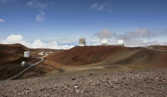 FILE - This Aug. 31, 2015, file photo shows telescopes on the summit of Mauna Kea on Hawaii's Big Island. Hawaii's Supreme Court upheld a decision to grant a construction permit for an embattled, international giant telescope project planned for a mountain Native Hawaiians consider sacred. The court ruling Tuesday, Oct.. 30, 2018, is a victory for the contentious Thirty Meter Telescope planned for Hawaii's tallest mountain, Mauna Kea. (AP Photo/Caleb Jones, File)