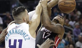 Charlotte Hornets' Willy Hernangomez (41) blocks a shot by Miami Heat's Rodney McGruder (17) in the second half of an NBA basketball game in Charlotte, N.C., Tuesday, Oct. 30, 2018. (AP Photo/Chuck Burton)