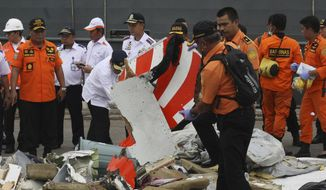 A rescuer inspects a part of Lion Air plane flight JT 610 retrieved from the waters where it's believed to have crashed at Tanjung Priok Port in Jakarta, Indonesia, Tuesday, Oct. 30, 2018. Relatives have provided samples for DNA tests to help identify victims of the Lion Air plane crash as accounts emerged Tuesday of problems on the jet's previous flight including rapid descents that terrified passengers. (AP Photo/Binsar Bakara)